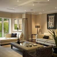 The elegant lounge of an expensive ground floor apartment in an exclusive new development, dressed as a show home by an interior designer. Cream, beige and bronze colours are the theme of the interior design. A contemporary chaise longue sits in the bay in front of the patio doors that lead out to the garden. The Artwork on the wall has a property release with iStock.